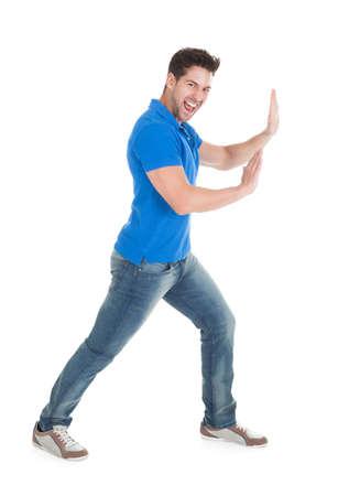 Volledig lengte portret van zelfverzekerde man duwen billboard over wit Stockfoto