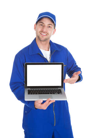 Young male mechanic displaying laptop over white  photo