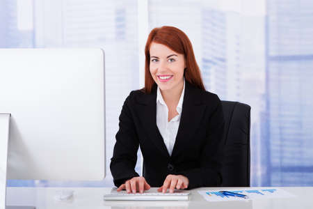 front office: Happy young businesswoman using computer at office desk Stock Photo