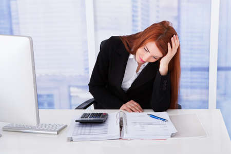 tired person: Tensed young businesswoman with paperwork at office desk