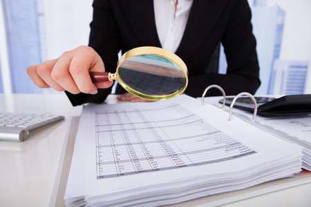 Midsection of young businesswoman scrutinizing bills with magnifying glass at office desk Stok Fotoğraf