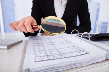 impuestos: Sección media de la joven empresaria examinar las facturas con lupa en el escritorio de la oficina