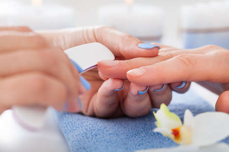 Cropped image of woman undergoing manicure process in beauty salon photo