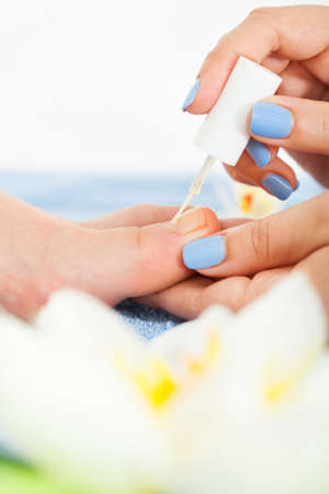 High angle view of pedicurist applying plain varnish on womans toenail at beauty salon photo