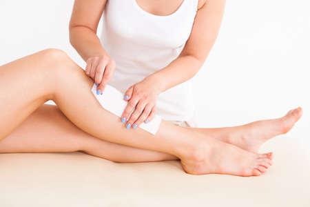 depilacion con cera: Secci�n media de la pierna femenina del cliente terapeuta encerado en el spa de belleza
