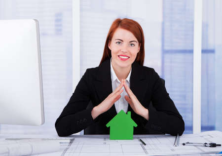 sheltering: Portrait of confident businesswoman sheltering green house model at office desk
