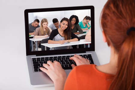 Cropped image of young female student attending online lecture on laptop at desk photo