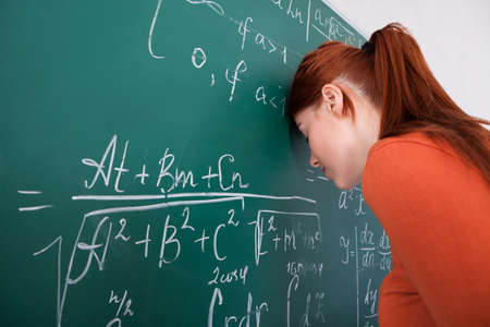 Side view of sad young female student leaning head on blackboard in classroom photo