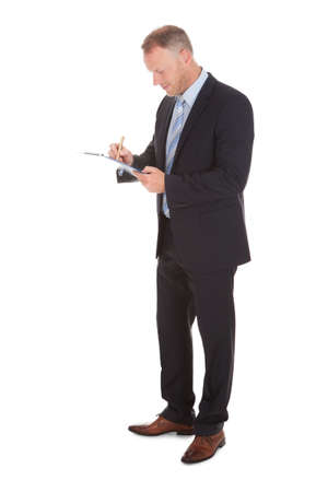 1 person: Full length of businessman writing on clipboard isolated over white  Stock Photo