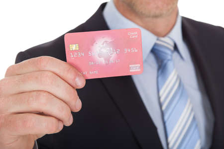 Portrait of confident businessman holding credit card over white  photo