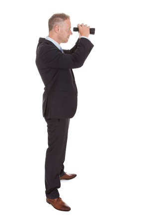 Portrait of confident mid adult businessman looking through binoculars over white  photo