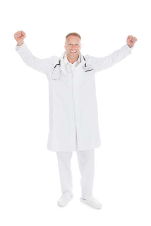 Full length of successful young male doctor with arms raised over white  photo