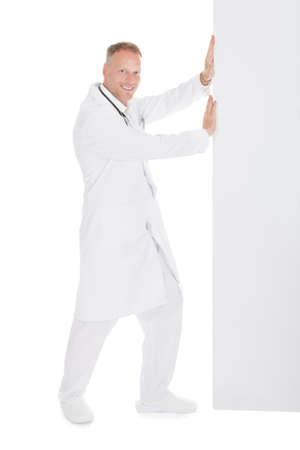 Full length side view of young male doctor pushing something over white  photo