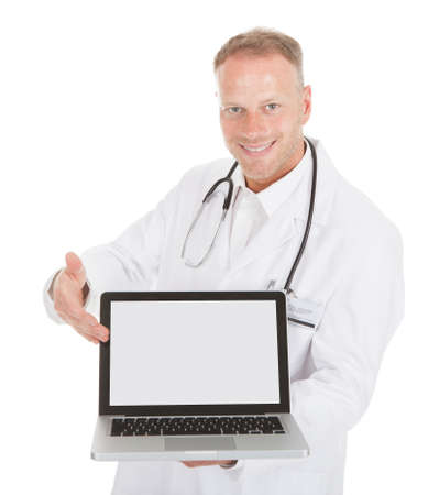 young male doctor: Portrait of smiling young male doctor displaying laptop over white