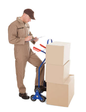 Full length of delivery man writing notes by stacked cardboard boxes on cart over white background