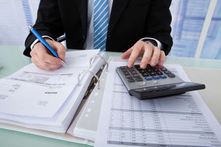 account executives: Midsection of young businessman calculating invoice at office desk