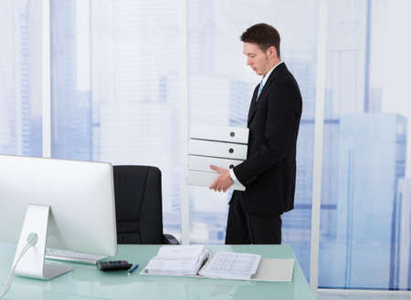 Side view of young businessman carrying stacked binders at office desk photo