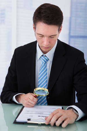 Young businessman examining invoice through magnifying glass at office desk photo