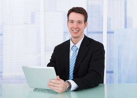 Portrait of confident young businessman using digital tablet at office desk photo