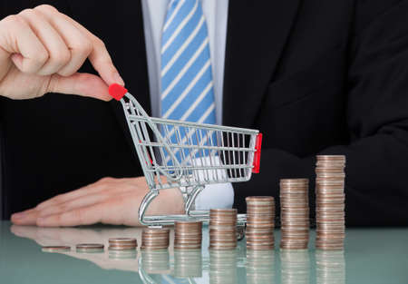 cart cash: Midsection of young businessman with shopping cart and coin stacks in office Stock Photo