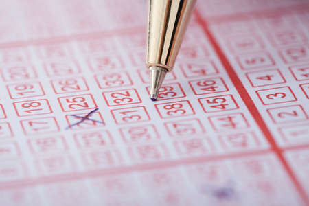 loto: Closeup of pen marking numbers on lottery ticket