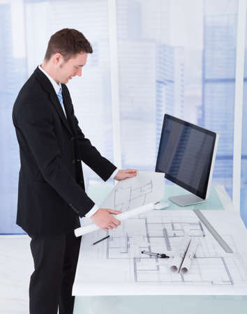 construction draftsman: Side view of young businessman looking at blueprint at computer desk in office