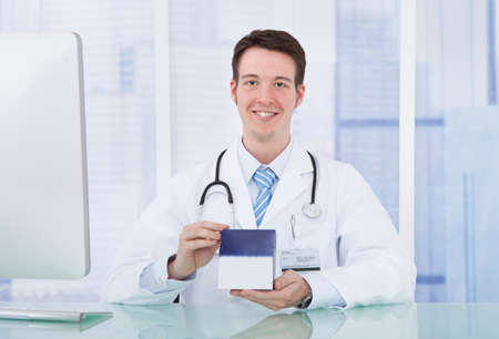 Portrait of confident young male doctor holding medicine box in hospital photo