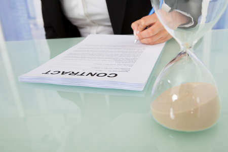 Midsection of young businesswoman signing contract with hourglass at office desk photo
