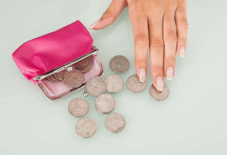 Midsection of businesswoman counting coins spilled from pink purse at office desk photo