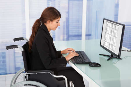 Side view portrait of handicapped businesswoman using computer while sitting on wheelchair in office photo