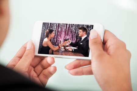 cropped image: Cropped image of businesswoman watching couple toasting wineglasses on cellphone over white  Stock Photo