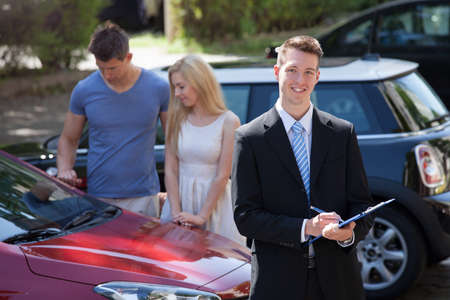 insurance agent: Young salesman writing on clipboard with couple looking at new car in background