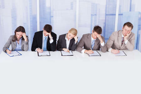 bored man: Group of tired corporate personnel officers at table in office
