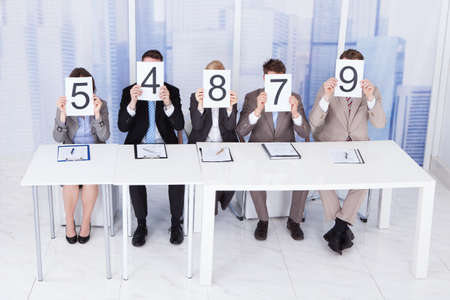score board: Portrait of confident business people showing score cards