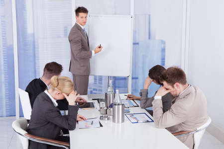 Colleagues getting bored during business presentation given by businessman in office