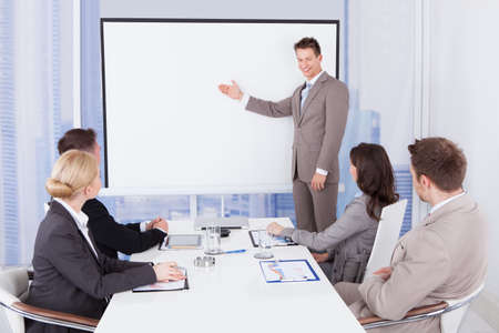Young businessman giving presentation to colleagues in office