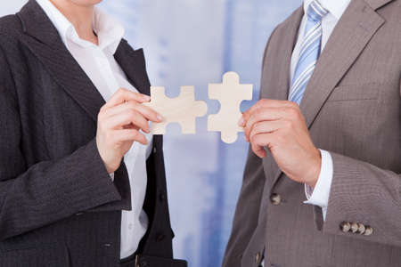 two piece: Midsection of businessman and businesswoman joining jigsaw pieces in office Stock Photo