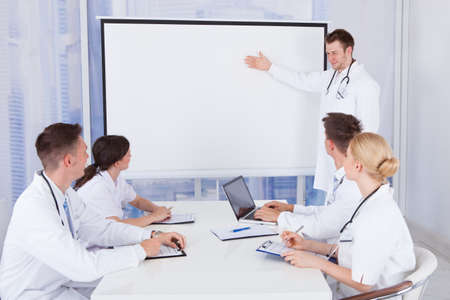 Young male doctor giving presentation to colleagues in conference room photo