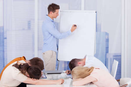 tired man: Colleagues getting bored during presentation given by businessman in office