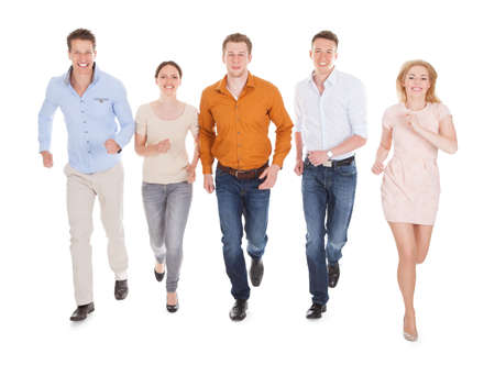 five people: Full length portrait of happy young friends running over white  Stock Photo