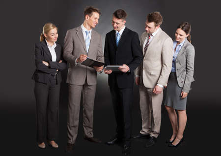 Happy business people discussing over clipboard while standing against black  photo
