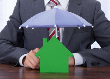 sheltering: Midsection of businessman sheltering house with umbrella at desk Stock Photo