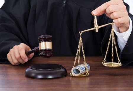 balanza en equilibrio: Sección media de juez masculino golpear el martillo mientras se mantiene la escala con el dinero en el tribunal Foto de archivo