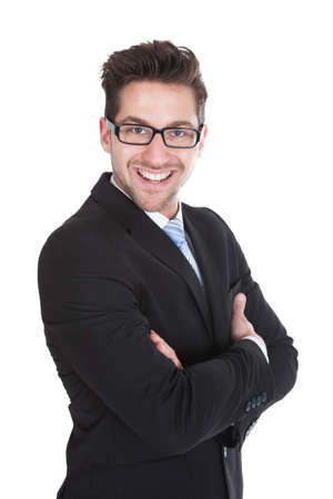 Portrait of smiling young businessman standing arms crossed over white  photo