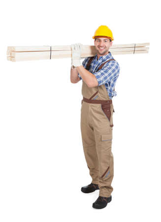 Full length portrait of young manual worker carrying wooden planks over white