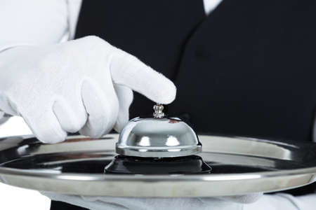 hand bell: Midsection of young butler holding service bell over white