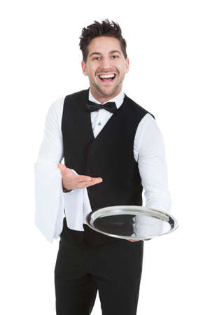 Portrait of smiling young waiter holding empty serving tray isolated over white  photo