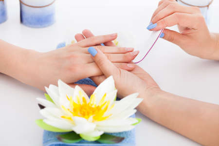 manicurist: High angle view of manicurist filing womans nails in beauty salon Stock Photo