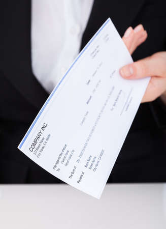 Midsection of smiling businesswoman holding cheque in office photo
