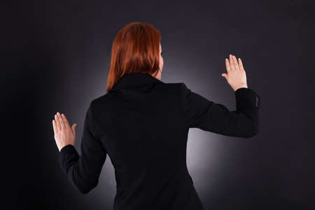 waistup: Rear view of young businesswoman gesturing against black